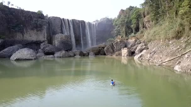 drone flies from waterfall along calm river with rocky banks
