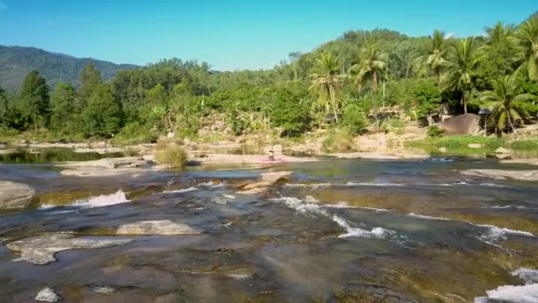 flycam moves fast above river rapids to woman on stone