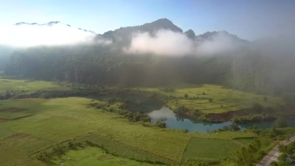 drone flies above countryscape with river to hills in fog