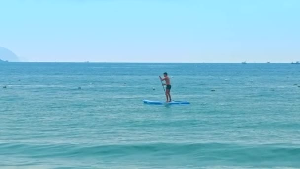 side view guy paddles sup standing on board against ocean