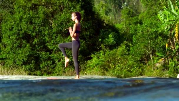 Side view lány áll a jóga jelent fa-patak partján