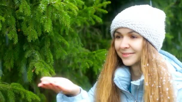 close view snowflakes fall on green spruce branches and young woman long loose flowing hair in knitted hat