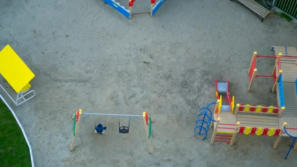 upper view nice playground with child on swing near wooden bright colored maze and houses in city park