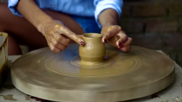 old potter guides lady fingers making clay pot on wheel