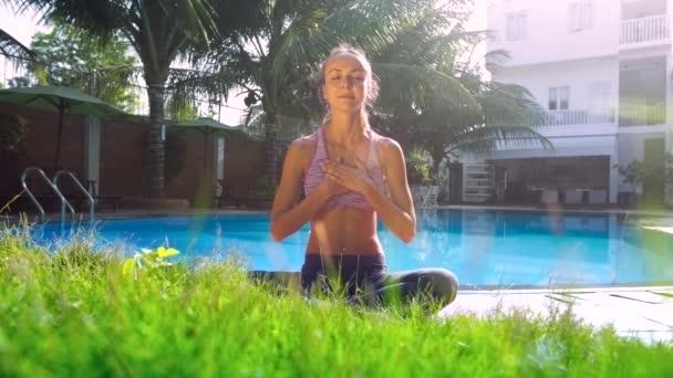 dívka v józe pozice uvolňuje uvedení ruce na hrudi u bazénu