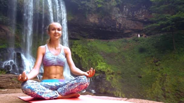 Mädchen in Lotuspose macht Atemübungen am Wasserfall