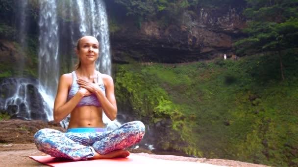 Mädchen in Lotus-Pose legt Hände auf Brust lächelt am Wasserfall