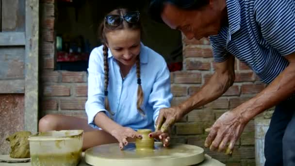 old master guides girl fingers making clay pot on wheel