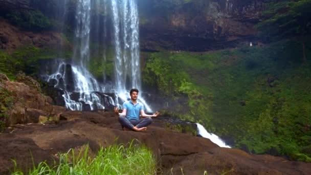 Konzentrierter Mann meditiert im Yoga Padma Asana am Wasserfall