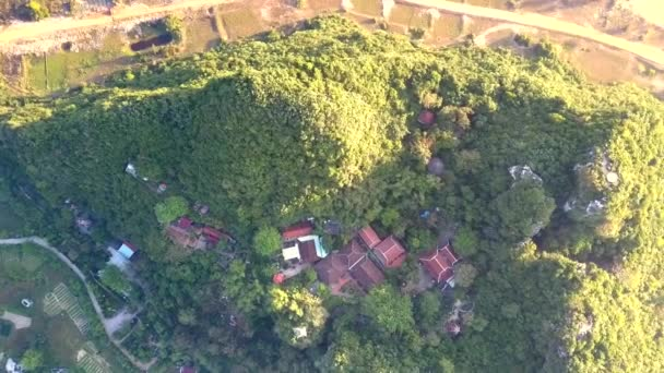 flight over temple buildings on hill surrounded by road