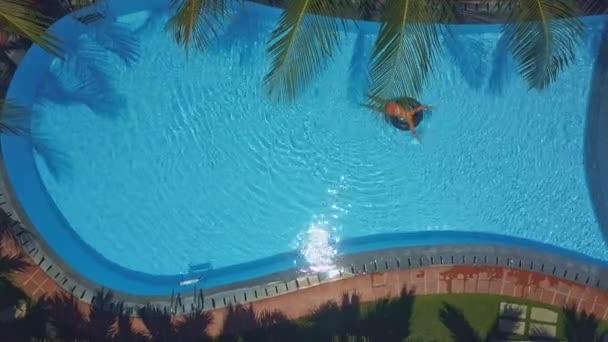 Schlankes Mädchen segelt auf Ring im Pool gegen Barriere
