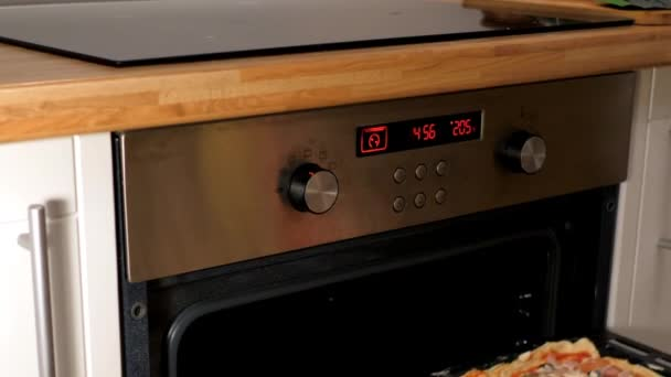 slow motion woman puts baking tray with pizza into oven
