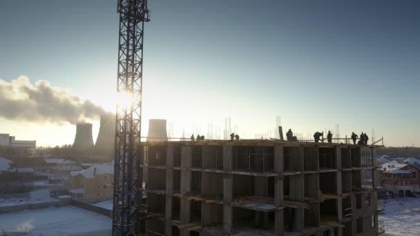 upper view sun shines through crane near working people