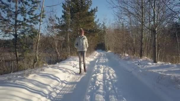 aerial woman in warm jacket enjoys hike in old winter forest