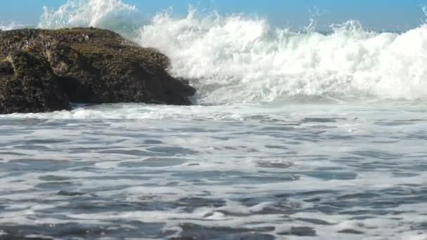 obrovské oceánské vlny se rozdrtí v hnědém kameni pomalu