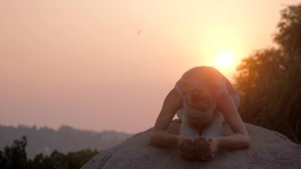 atletická dívka ohýbá tělo v asaně na obrovské kamenné pomalé pohyby