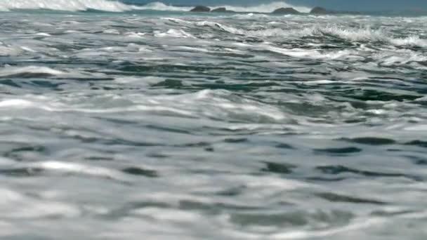 ohromné rugánské vlny se převalují na hnědých skalách pomalu