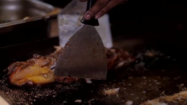 asijský kuchař se otáčí v olivovém oleji lahodné mořské ryby