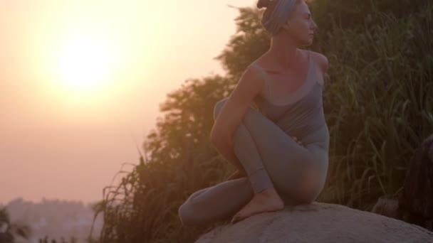 dáma sedí v matsyendrasana Asana na starém skalním pomalém pohybu