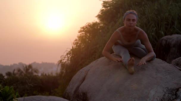 dáma rozohýbá tělo v józe Asana, pomalu se na kamenném pohybu