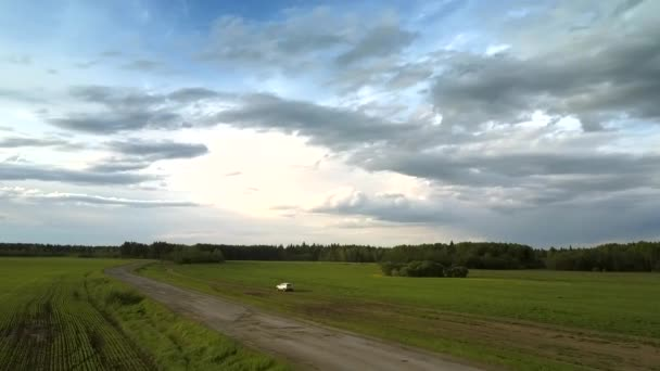 bílé moderní auto jezdí po pozemních silnicích blízko pole
