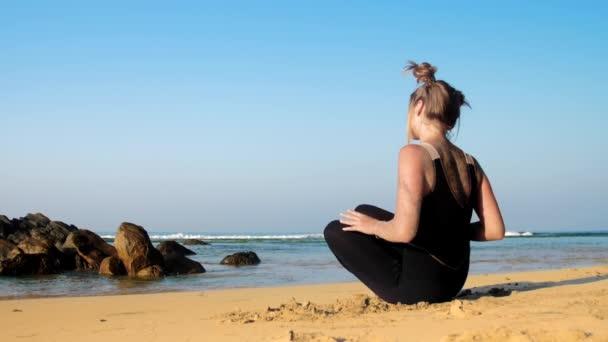 dívka mění polohu jómu na pláži proti modrému oceánu