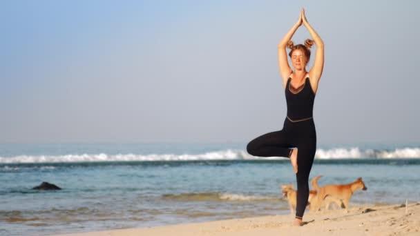 schöne blonde Dame im schwarzen Trainingsanzug macht Yoga-Pose
