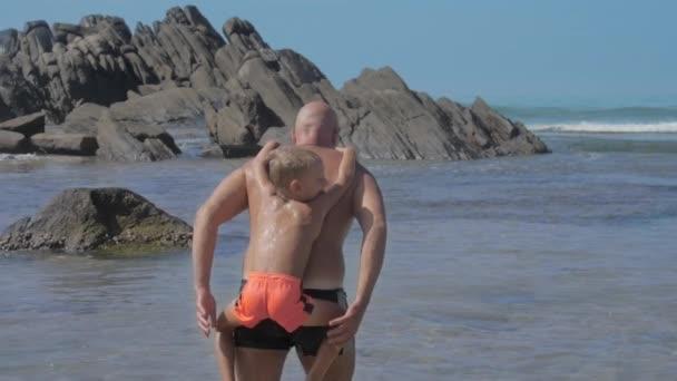 boy hangs on father shoulders spending time on ocean beach