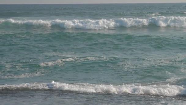 obrovské mořské vlny se převalují na pláži proti modrému nebi pomalý pohyb