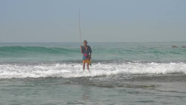 fisherman walks along water surf edge at foaming ocean waves