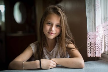 Portrait of cute ten-year-old girl posing for the camera sitting at the table.
