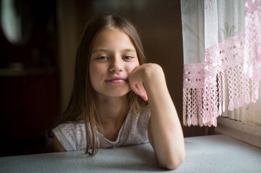 Portrait of cute ten-year-old girl sitting at the table.