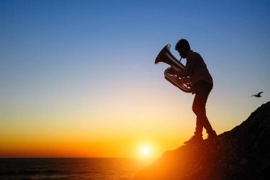 Silhouette of a musician play on Tuba on sea shore at sunset .