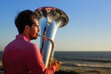 Musician playing the Tuba on the ocean coast.