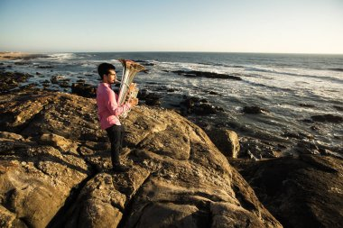 Musician play to Tuba on romantic sea shore.