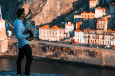 Musician play music on trumpet in front of Douro river at downtown of Porto, Portugal.