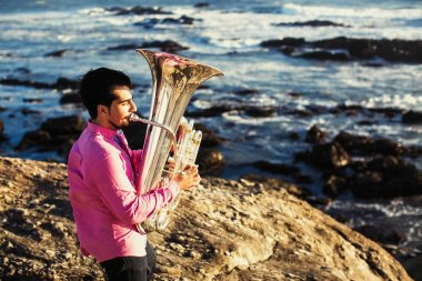 Musician play to Tuba on ocean shore.
