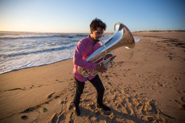 Young musician with a tuba playing on the sea beach.