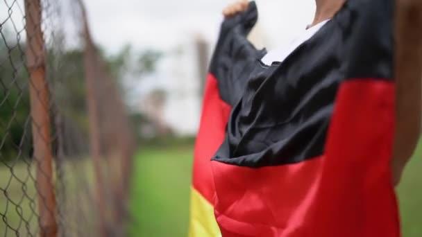 Německý fanoušek slaví během fotbalového zápasu