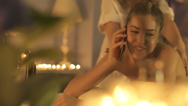 Krásná žena v lázních používá svůj telefon