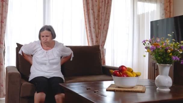 Zralá žena trpící bolestmi zad doma. Masáž dolní s rukama, pocit vyčerpání, stojící v obývacím pokoji. Zpomalený pohyb 4k