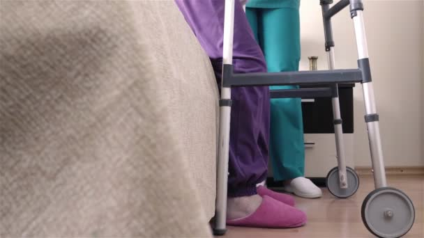 Friendly caregiver helping senior woman getting up from bed and walk with a walker. Home or hospice nursing and assistance concept. Slow motion 4K