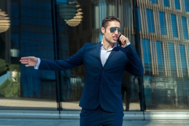 Angry business man in sunglasses talking on cell phone in front of modern building