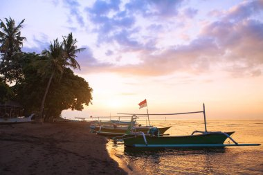 beautiful beach in Bali at sunset, exotic landscape with boats and palm trees
