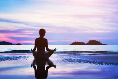 beautiful yoga background, silhouette of woman meditating on the beach at sunset