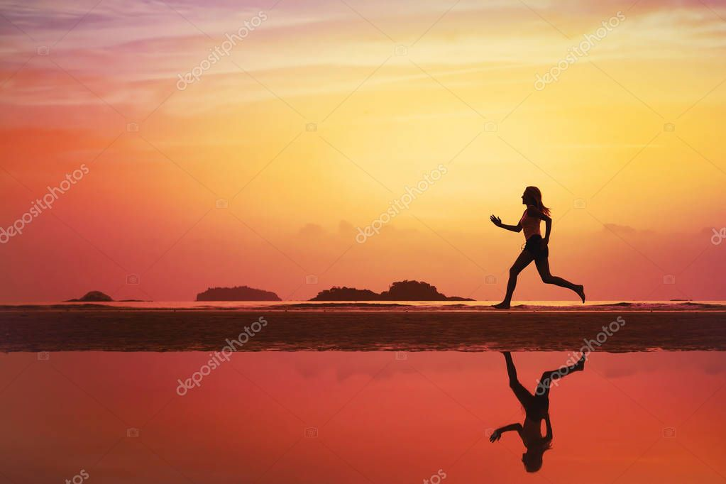 beautiful woman running on the beach at sunset, silhouette of sportive girl with reflection and place for text