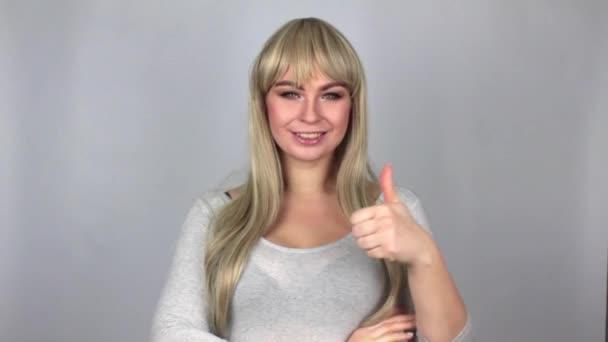 Krásná blondýnka zobrazeno velký prst do kamery nad šedým pozadím ve studiu