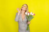Szőke nő kockás ruhában gazdaság tulipán csokor felett sárga háttér