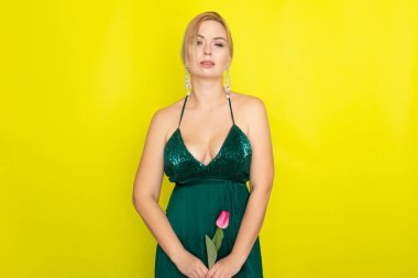 Blonde woman in green evening dress holding one tulip in her hands over yellow background