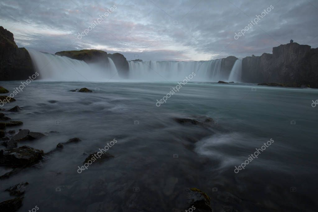 a waterfall in iceland between the mountains from the river spring